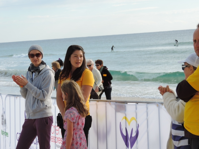 Draga Bebek, founder of Get On Board, Alana Spencer and a young supporter at the finish line greeting runners.