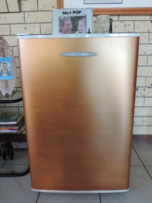 Looks like a flashy gold fridge but it was plain white and has been pained with cheap metallic paint from the variety store.