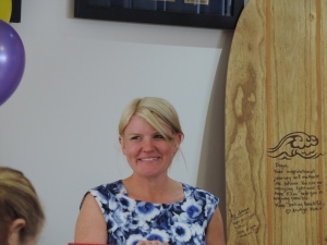 Kate next to the wooden surfboard.