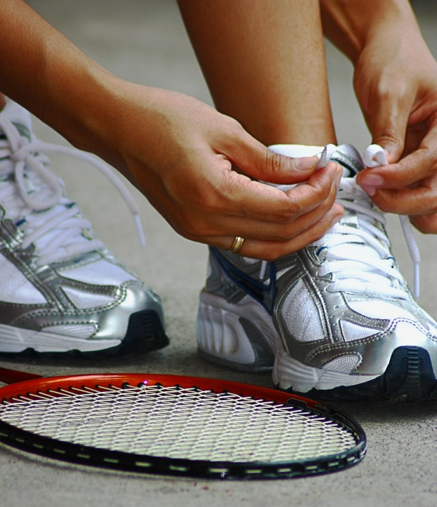 Tying Shoe Laces Securely Ready For A Game Of Badminton